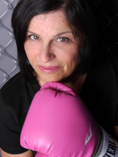 Nadine Vogel close-up facial image, pink boxing-glove held to chin